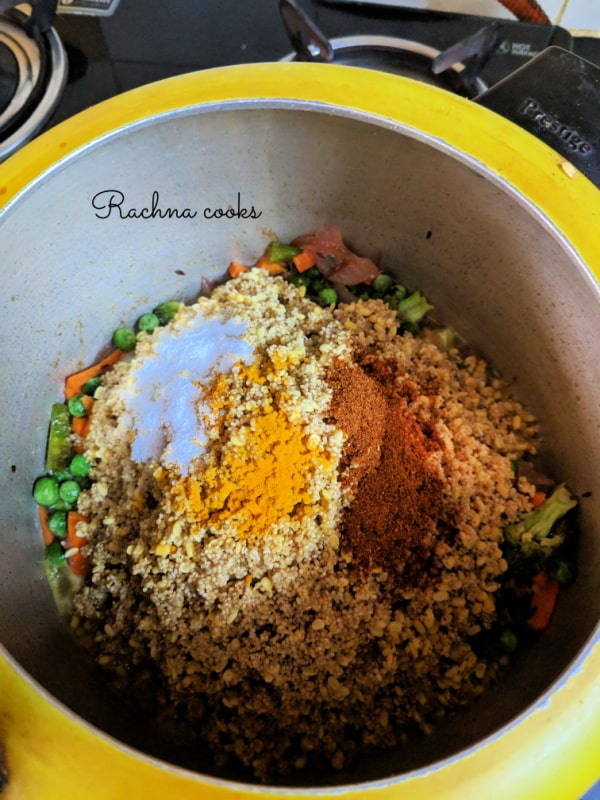 Millets and lentils are added on some veggies with salt, turmeric and garam masala powder