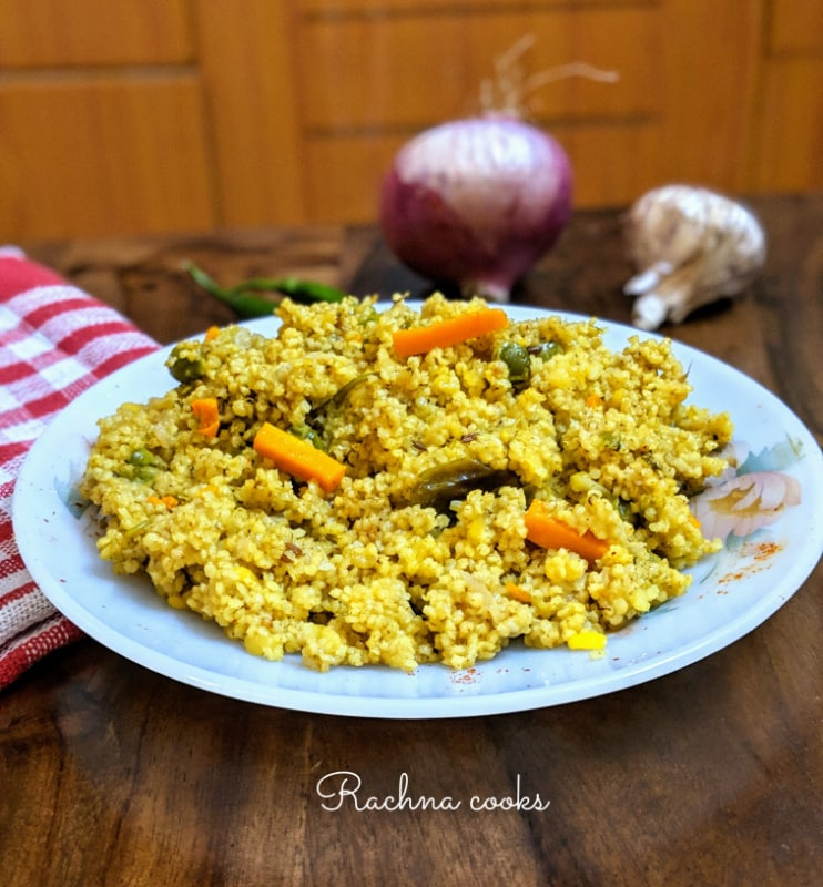 This picture shows a plate of foxtail millet khichdi with carrots and peas and some spices in the background.