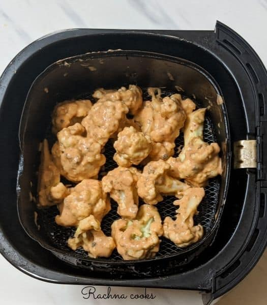 A single layer of coated cauliflower florets in air fryer basket