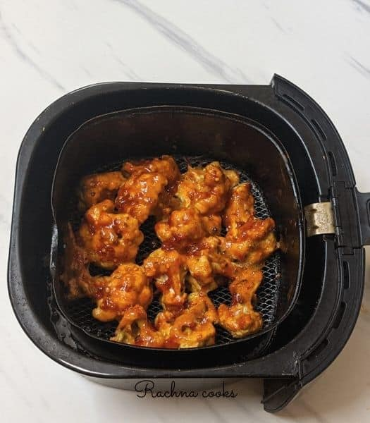 Air fried cauliflower florets in air fryer basket brushed with buffalo sauce